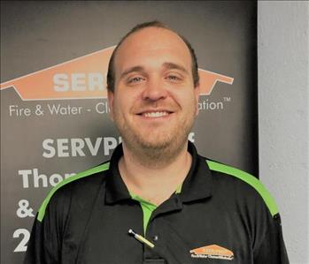 Young man, tall with short hair and scruffy beard in Servpro uniform